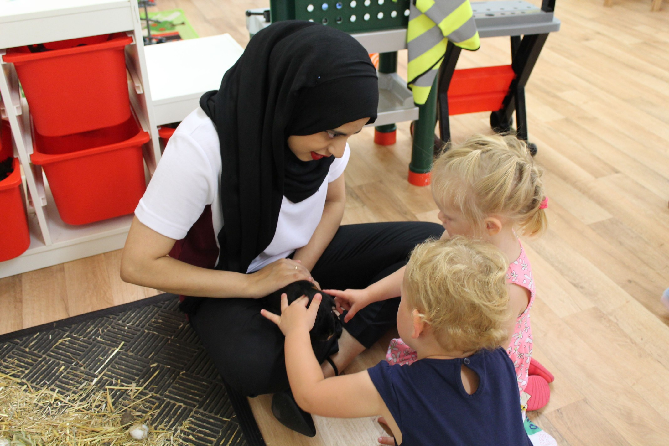 Saliha using the nursery guinea pig to teach the children different concepts and vocabulary.