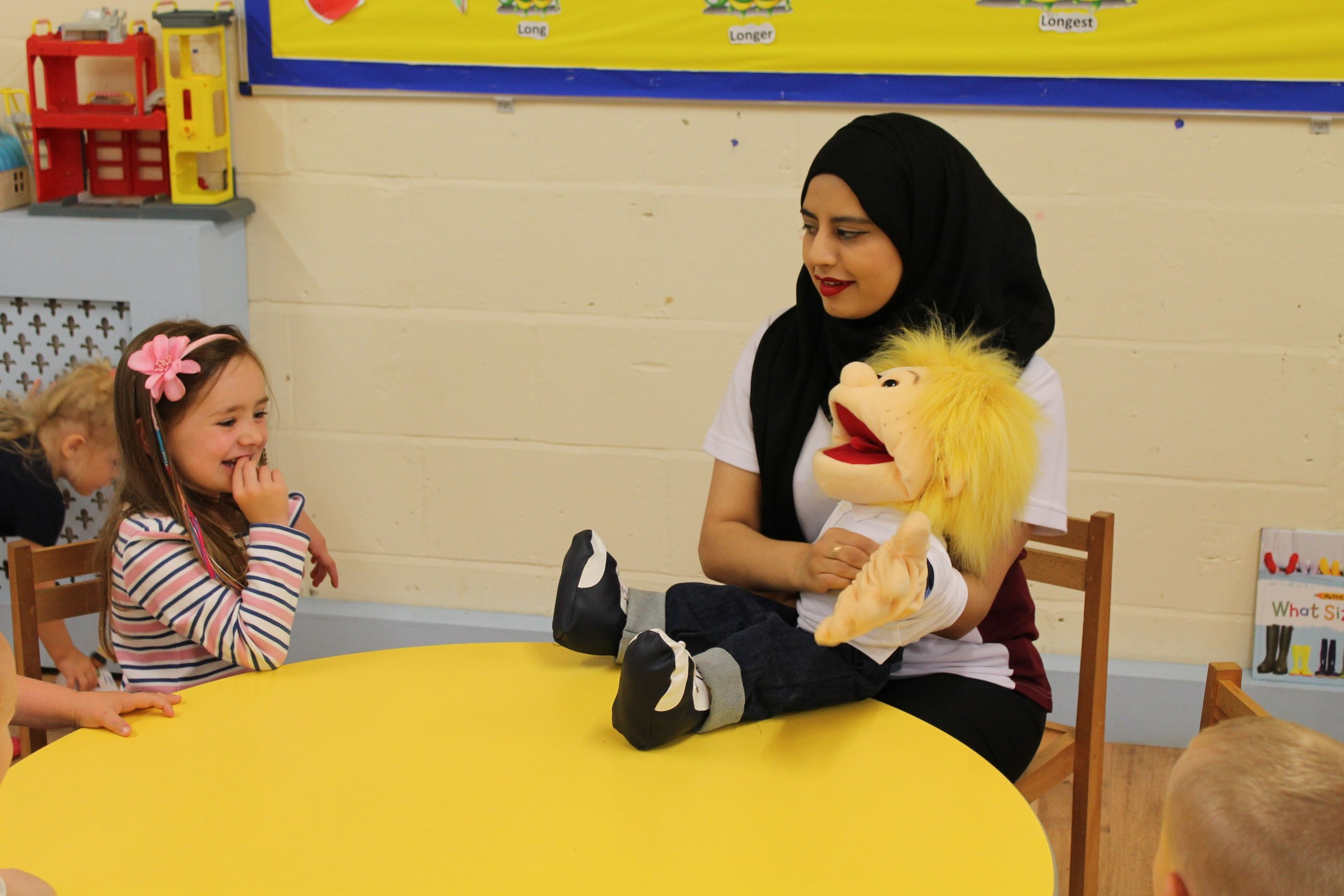 Saliha using puppets to help children develop the 'p' sound.
